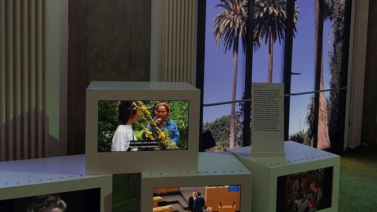 Ausstellung zeigt  Würfel im Raum mit Videos. Im Hintergrund ein künstliches Fenster mit Blick auf Palmen vor einem tiefblauen Himmel.