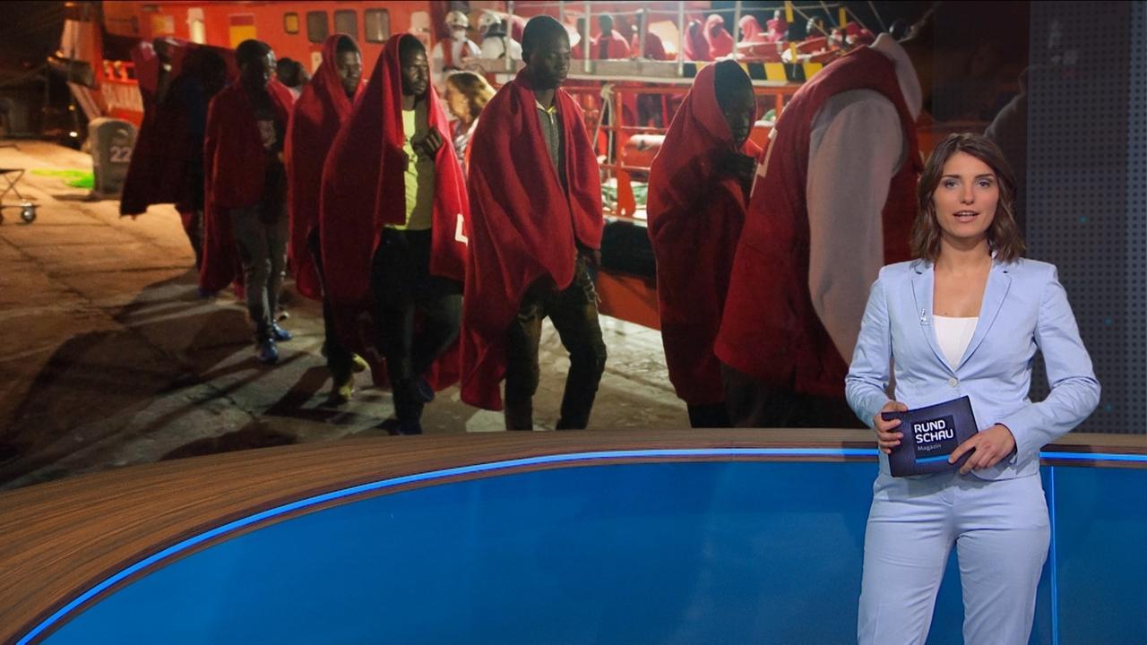Sandra Rieß vor Bild mit Bootsmigranten