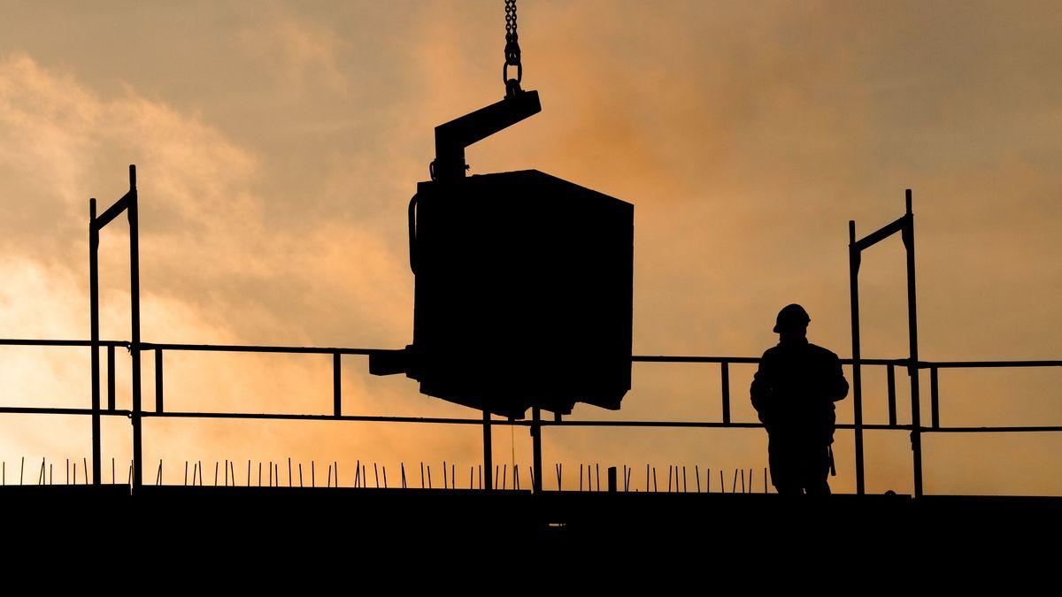 Bauarbeiter bauen bei Sonnenaufgang an einem Wohnhaus.