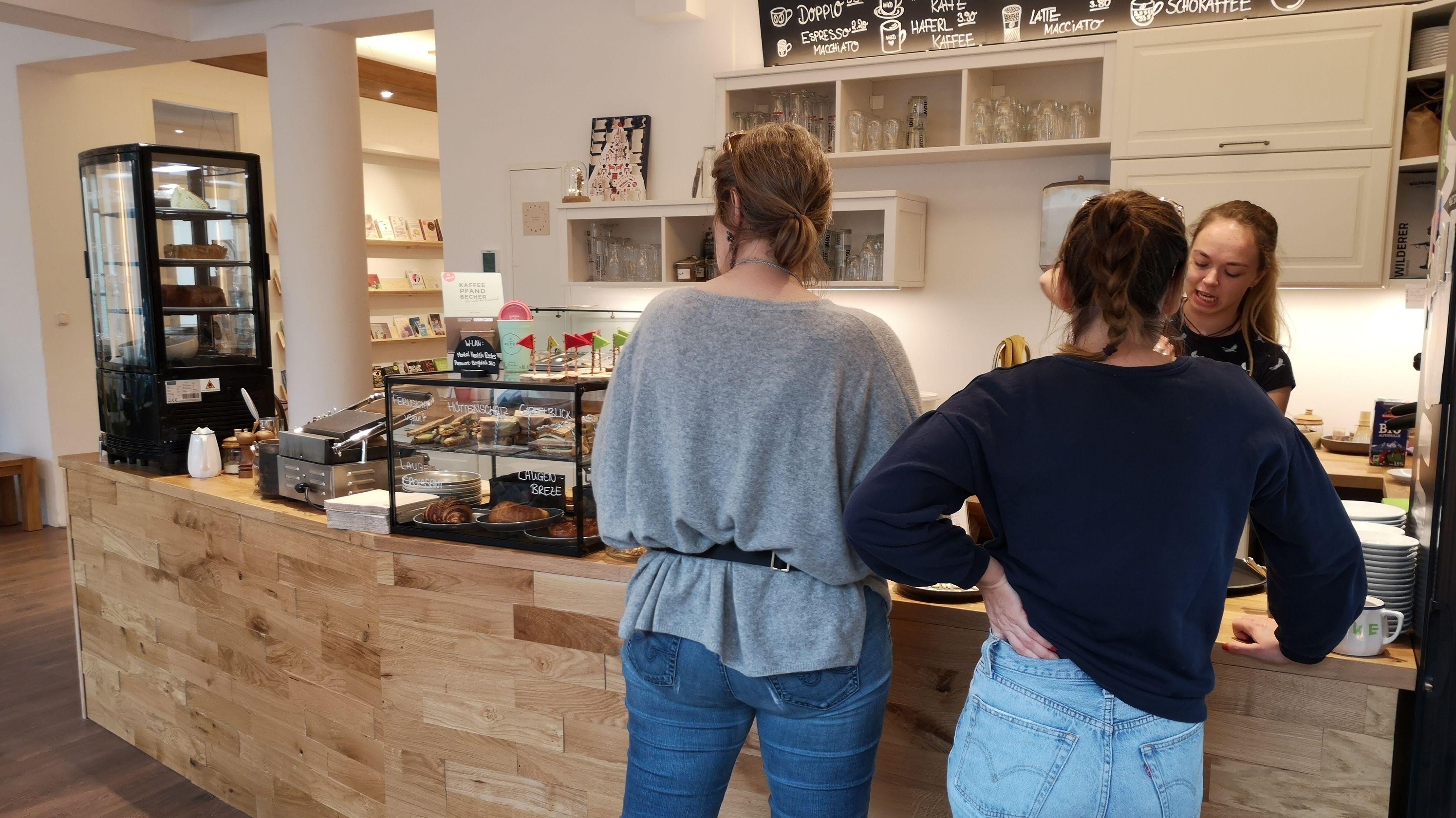An der Theke im Eingangsbereich warten zwei Kundinnen auf ihren Kaffee. Daneben steht eine Vitrine mit belegten Broten und Kuchen.