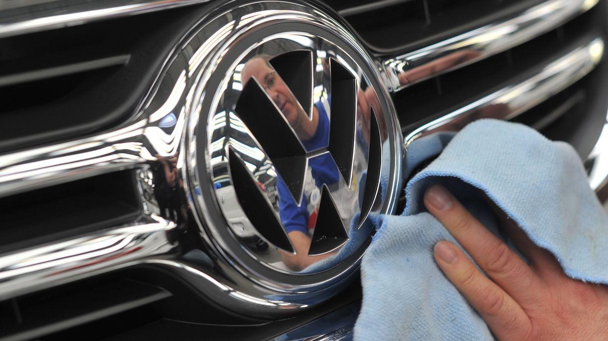 Ein VW Mitarbeiter poliert im Volkswagen Stammwerk in der Endkontrolle das VW-Logo eines Wagens.