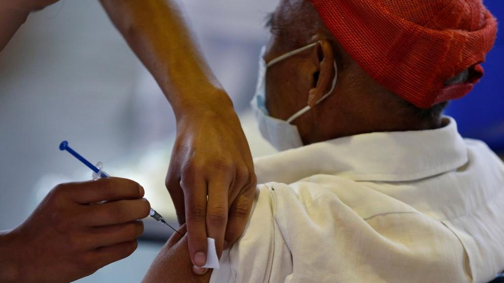 Impfungen weltweit - Symbolbild: Mexiko-Stadt: Ein medizinischer Mitarbeiter impft einen Mann | Bild:Rebecca Blackwell/AP/dpa