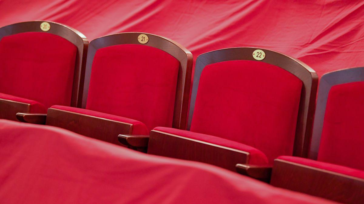 Leere Theater-Sitzplätze und mit roten Tüchern abgedeckte Plätze