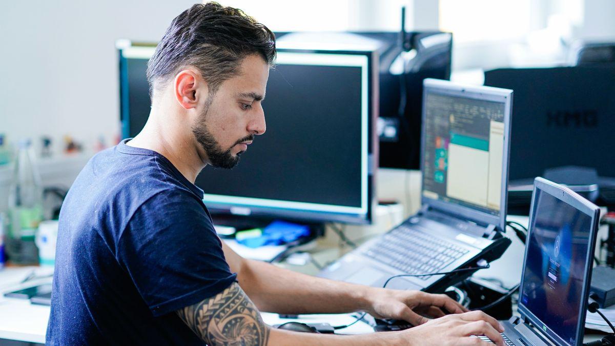 Ein Fachinformatiker für Systemintegration arbeitet in einem Büro an mehreren Computern.