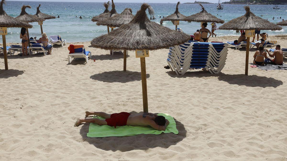 Ein Mann liegt unter einem Sonnenschirm am Strand von Cala Major