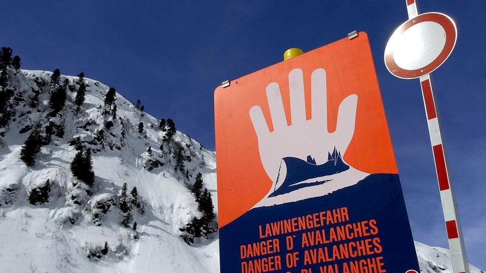 Lawinenwarnschild vor einem verschneiten Berg | Bild:picture-alliance/dpa