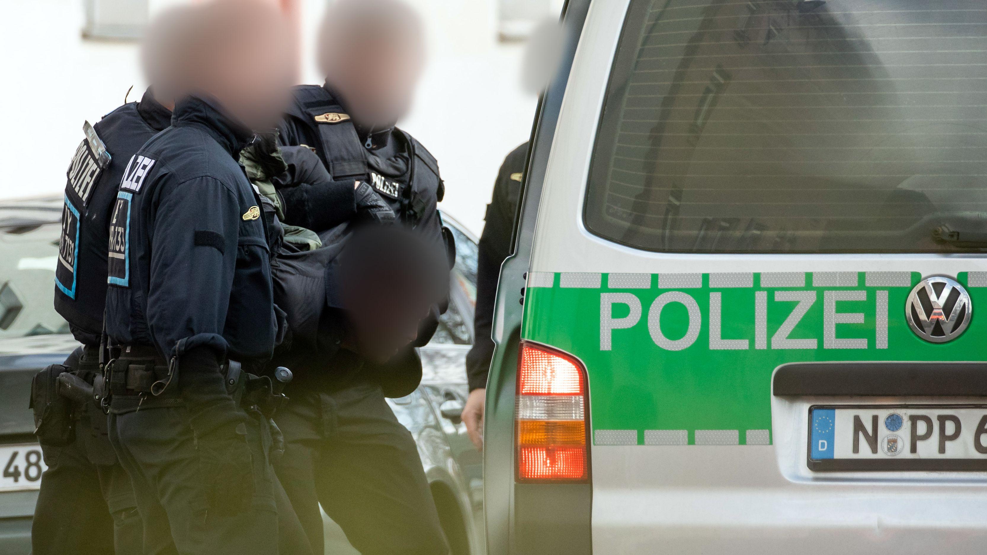Einsatzkräfte der Polizei führen in Nürnberg einen Mann ab, der vor seiner Abschiebung geflohen war.