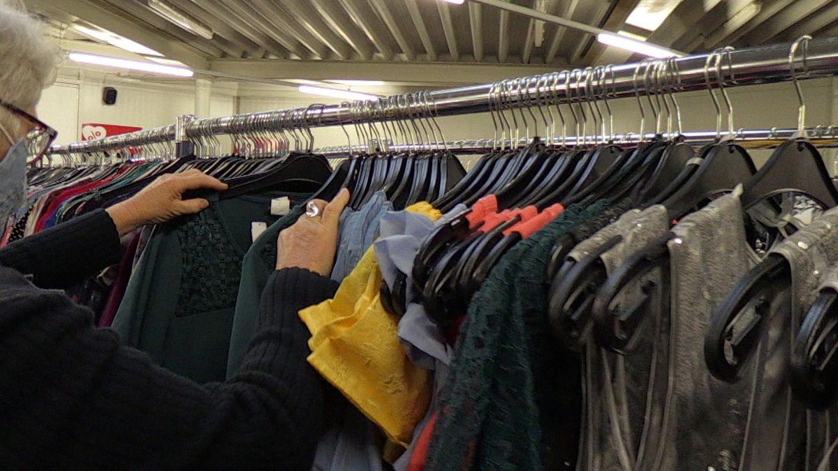 Eine Frau schaut in einem Kleidergeschäft Oberteile durch