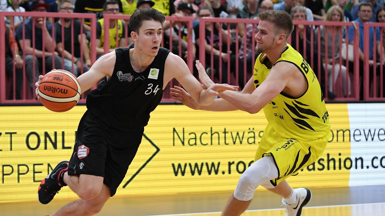 Basketballspieler in schwarzem Trikot mit Basketball und Basketballspieler in gelbem Trikot vor Zuschauern