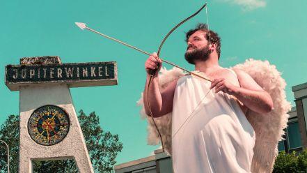 Mann im Amor-Kostüm hält Pfeil und Bogen