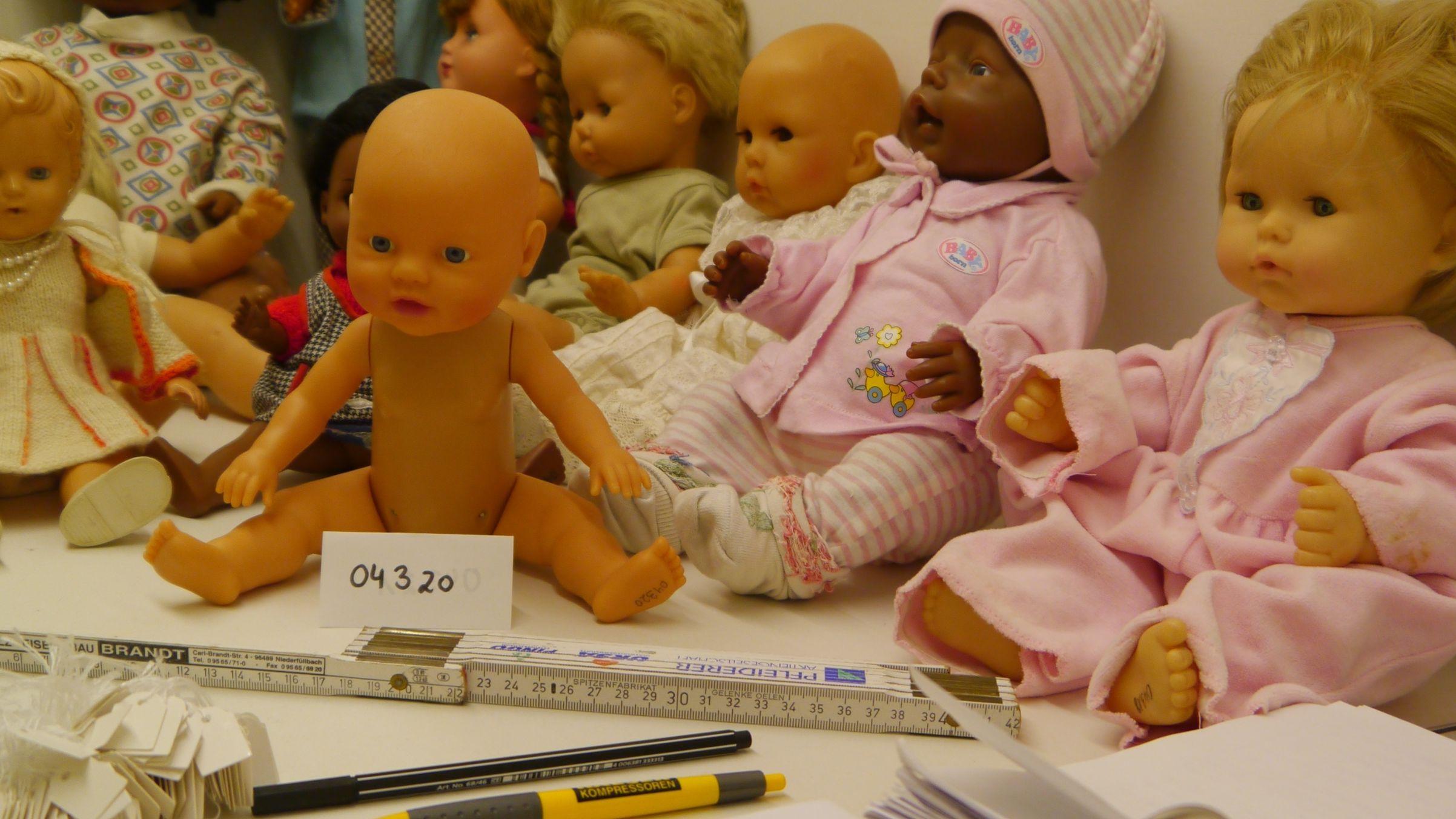 Auf einem Tisch sitzen mehrere Puppen, davor ein Zollstock und Stifte für die Inventarisierung der Puppen.