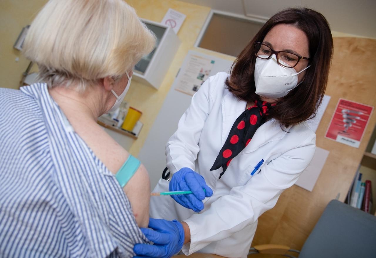 30.03.2021, Baden-Württemberg, Pforzheim: Nicola Buhlinger-Göpfarth (r), Fachärztin für Allgemeinmedizin, impft in ihrer Praxis eine Patientin gegen das Coronavirus. Dabei wird der Impfstoff von Biontech/Pfizer genutzt.