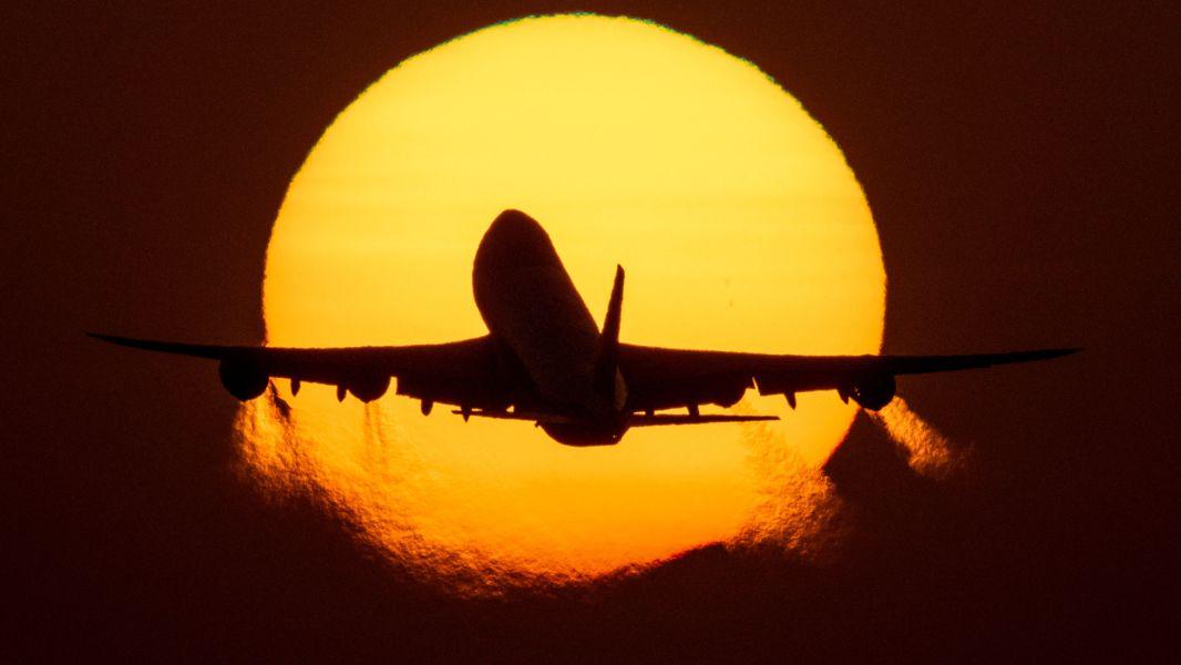 Flugzeug fliegt  in den  Sonnenaufgang