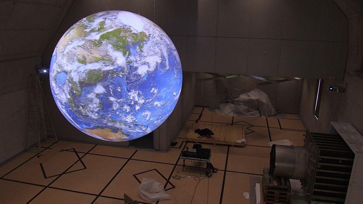 Das Modell eines blau leuchtenden Globus in einem Raum.