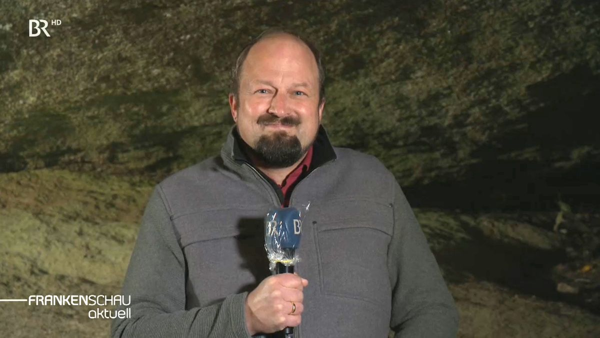 BR-Reporter Lorenz Storch mit einem Mikrophon in der Hand über ein mögliches Atommüll-Endlager, im Hintergrund Granitfelsen.