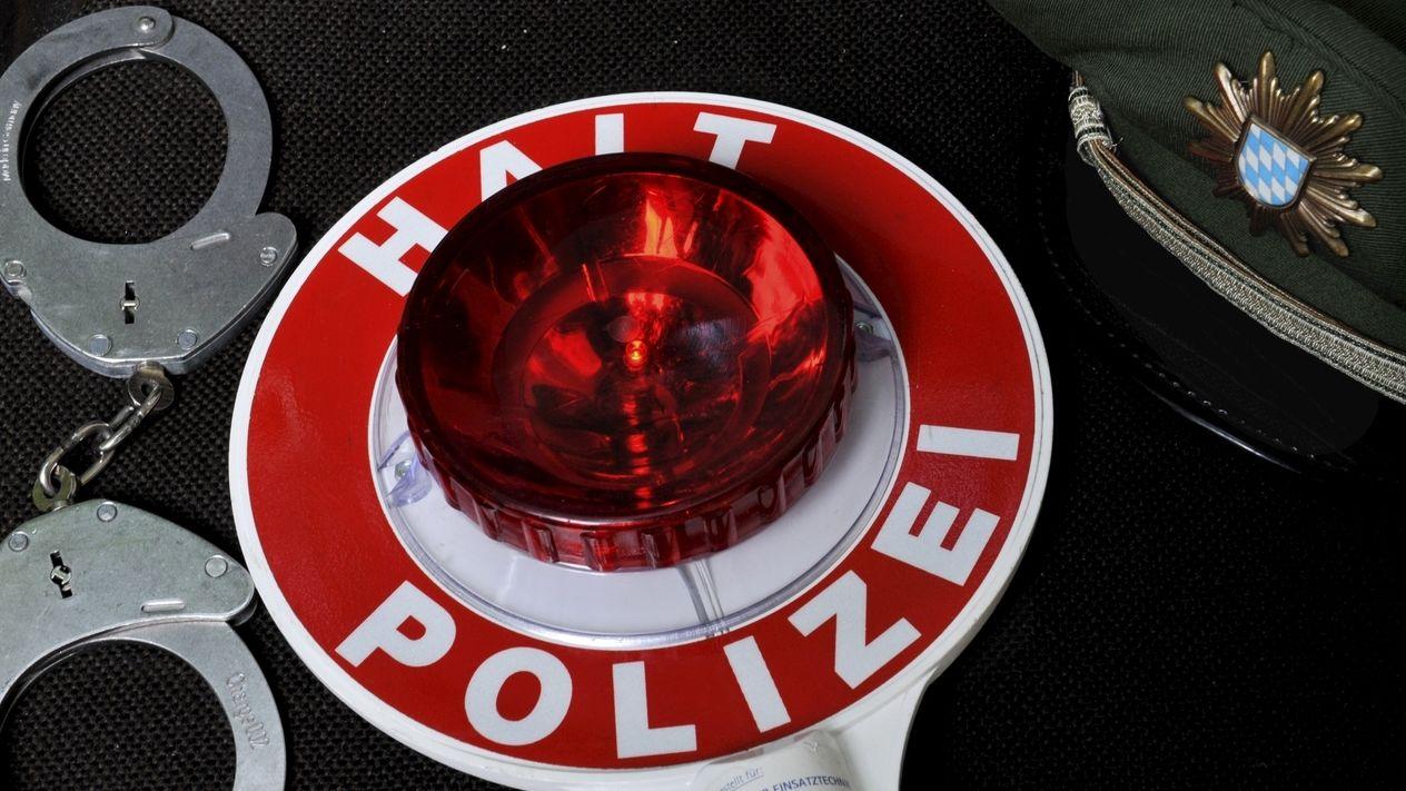 Handschellen liegen neben einer Polizeikelle und einer Mütze mit dem Wappen der bayerischen Polizei