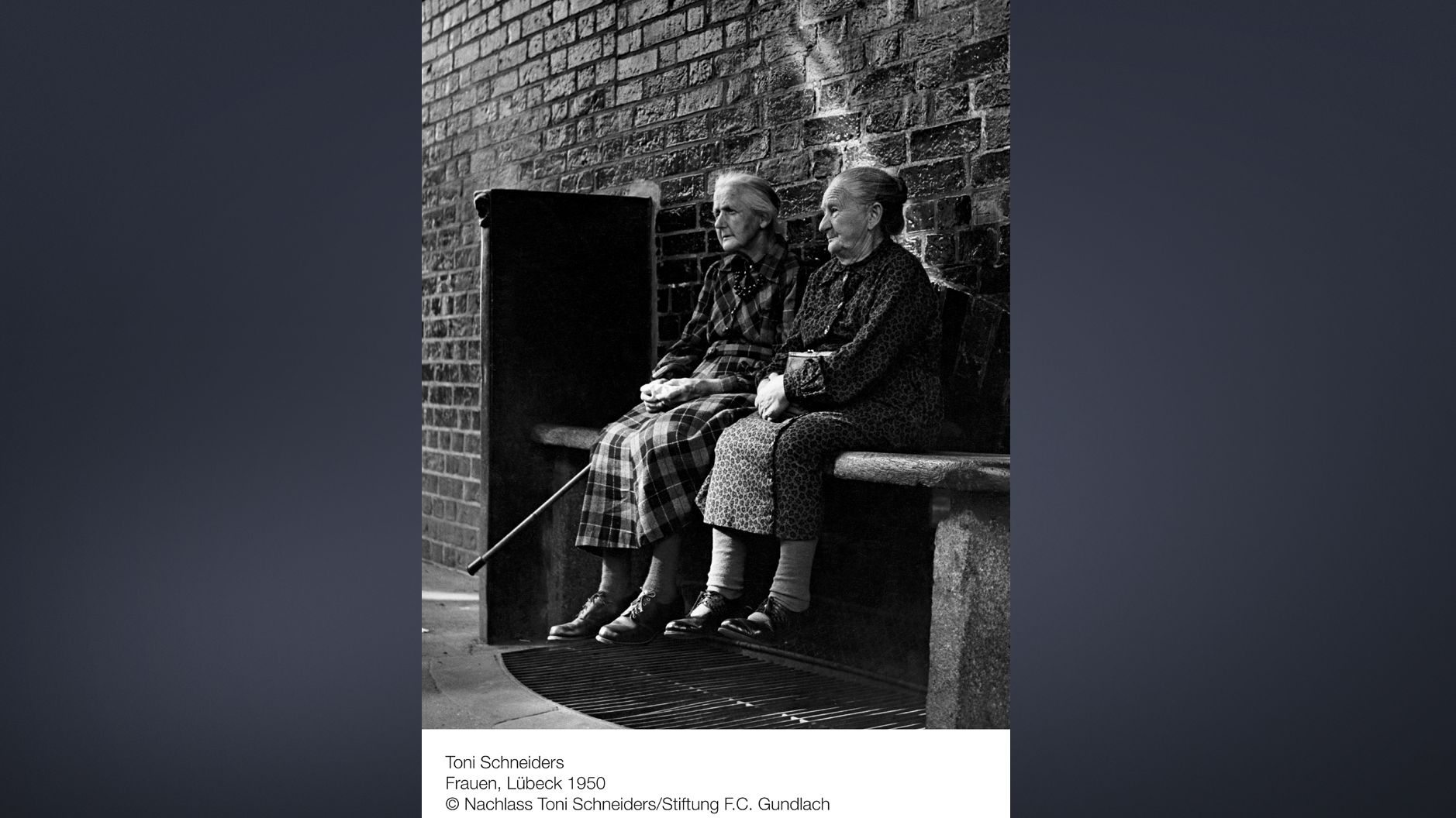 Schwarzweiß-Foto von zwei alten Frauen auf einer Bank an der Hauswand