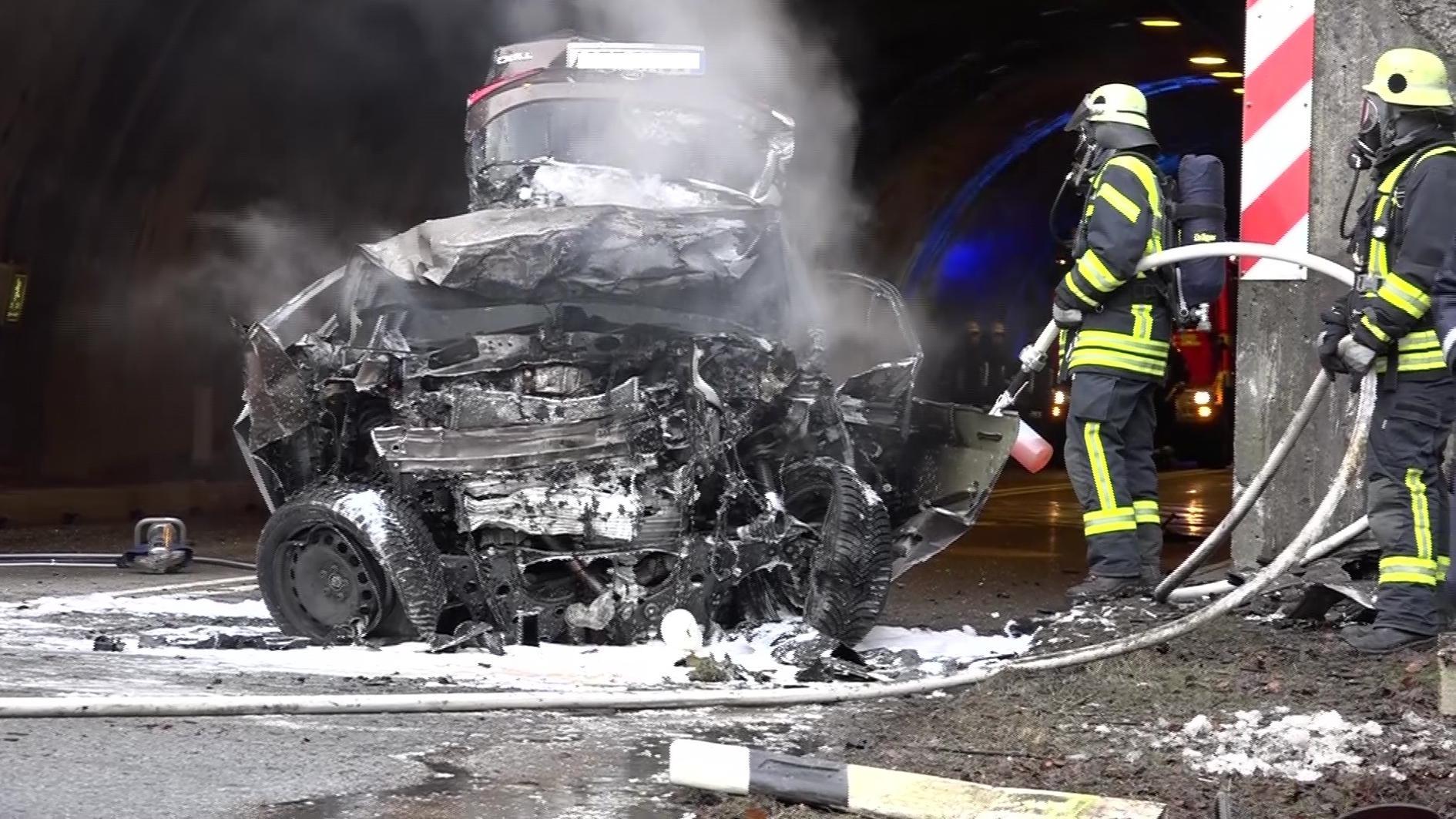 Zwei Feuerwehrmänner stehen neben dem ausgebrannten Autowrack.
