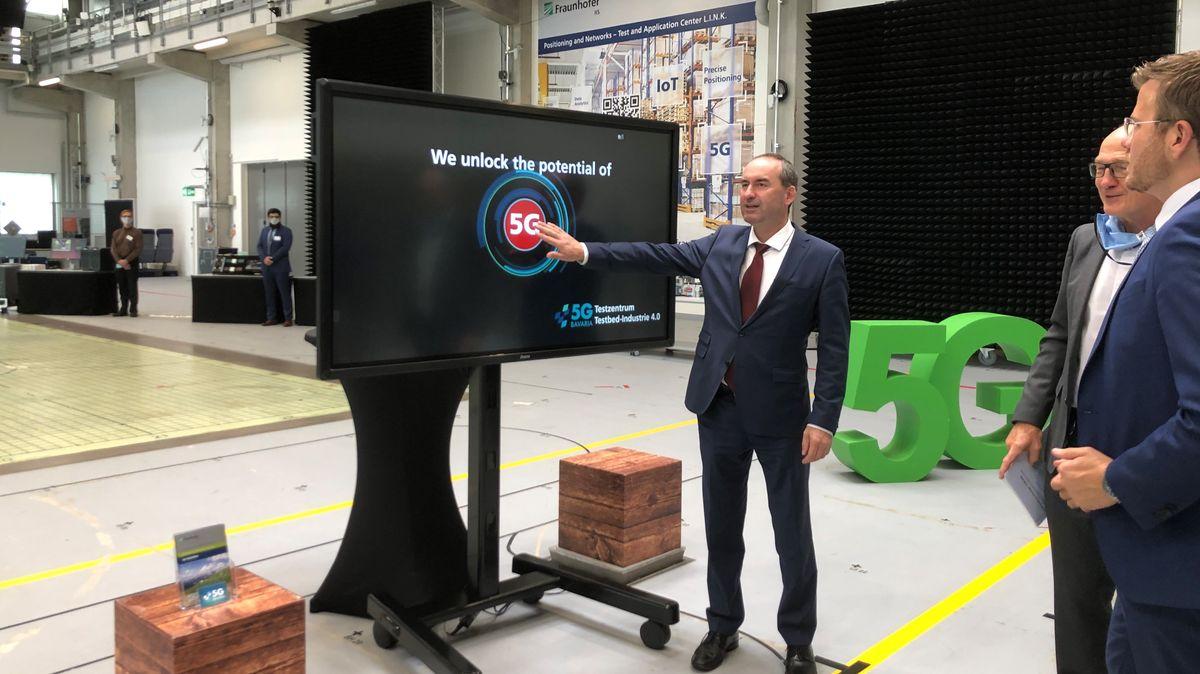 """Hubert Aiwanger steht vor einem großen Bildschirm, der """"5G"""" anzeigt."""