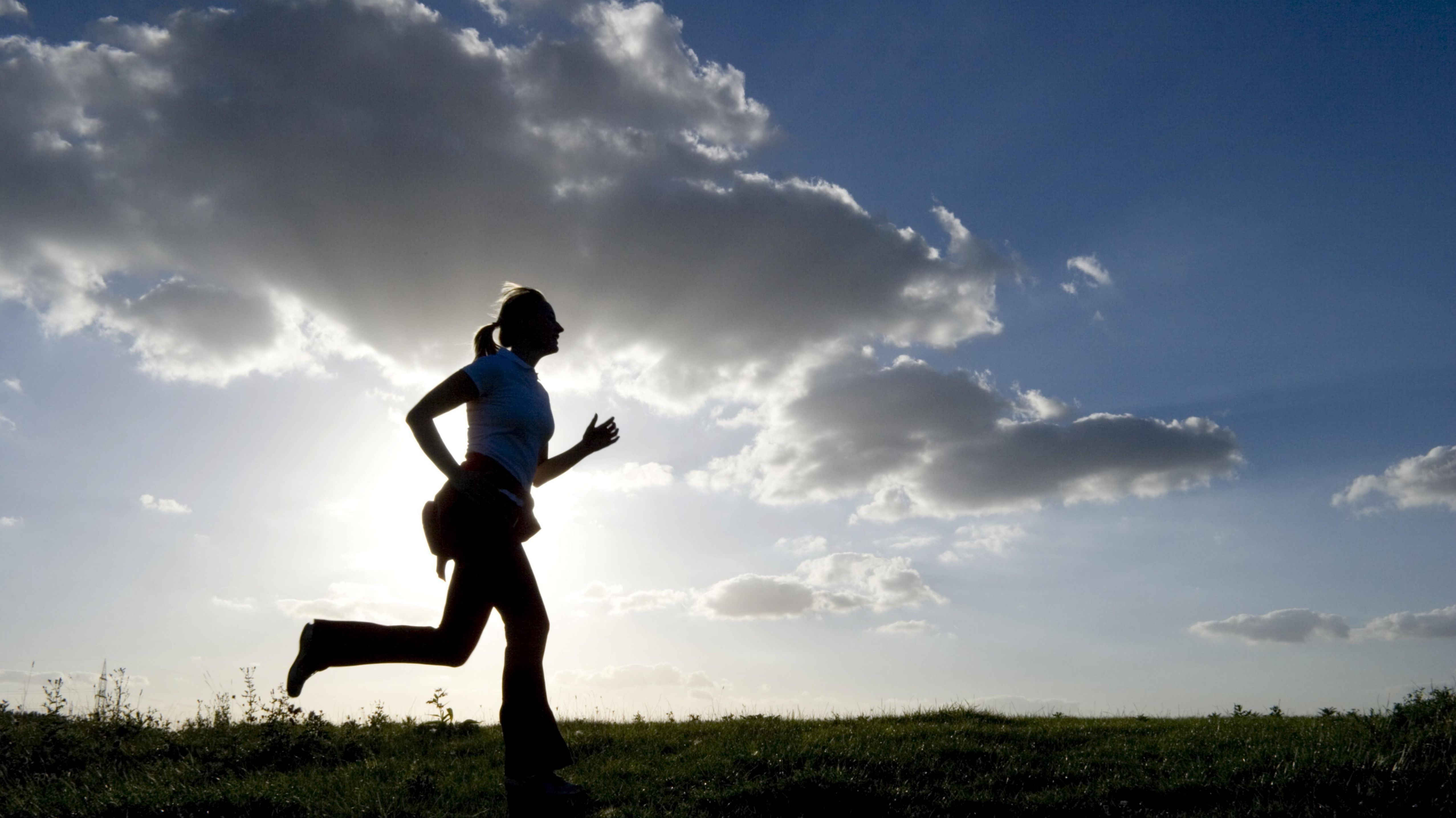 Symbolbild: Frau läuft vor blauem Himmel im Gegenlicht.