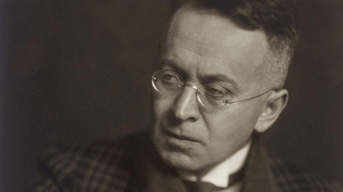 Mann mit Nickelbrille und Stirnfalte in kariertem Jacket: Karl Kraus im Jahr 1928.