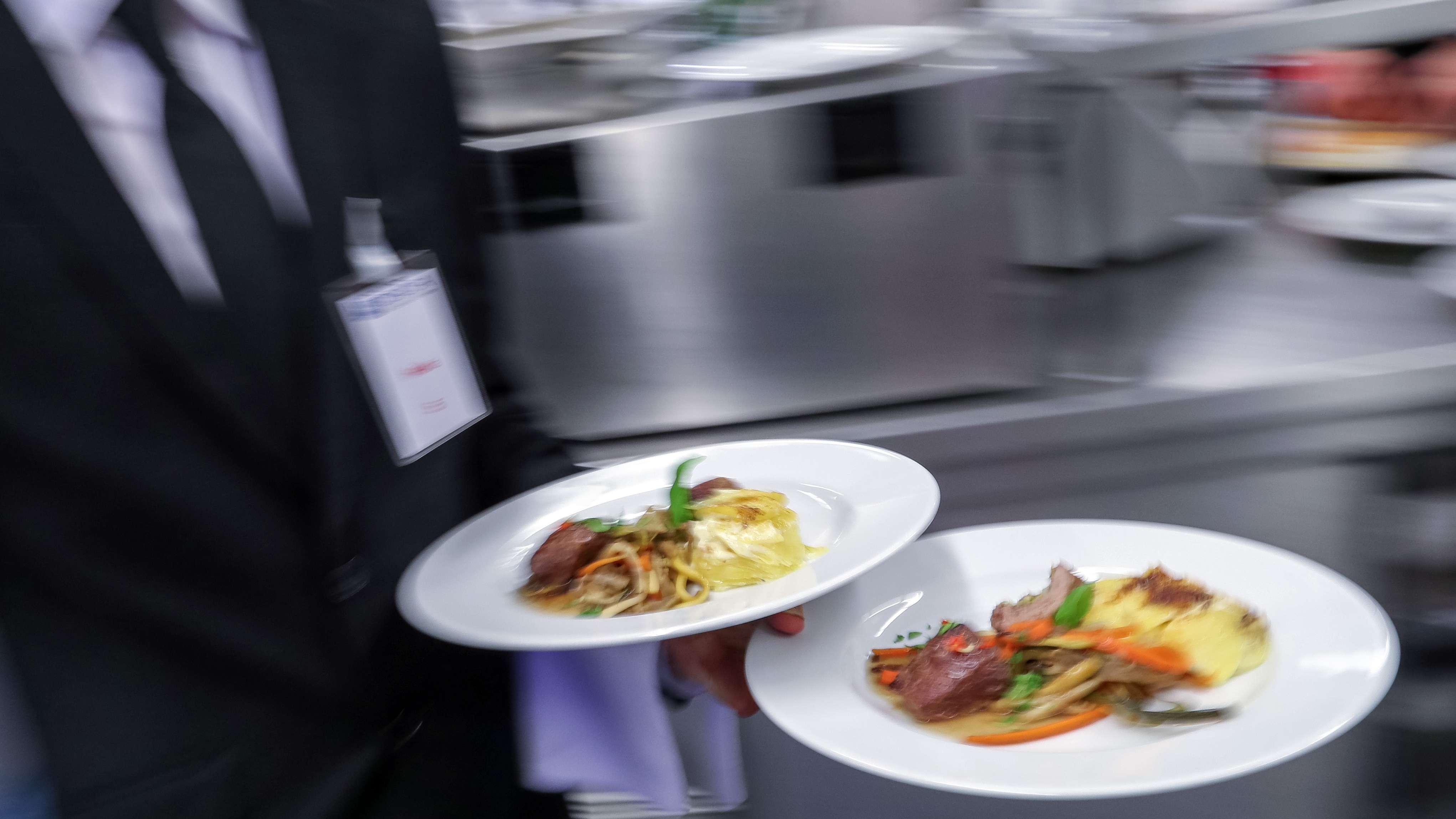 Ein Kellner trägt zwei Teller mit Essen von der Küche ins Restaurant (Symbolbild)