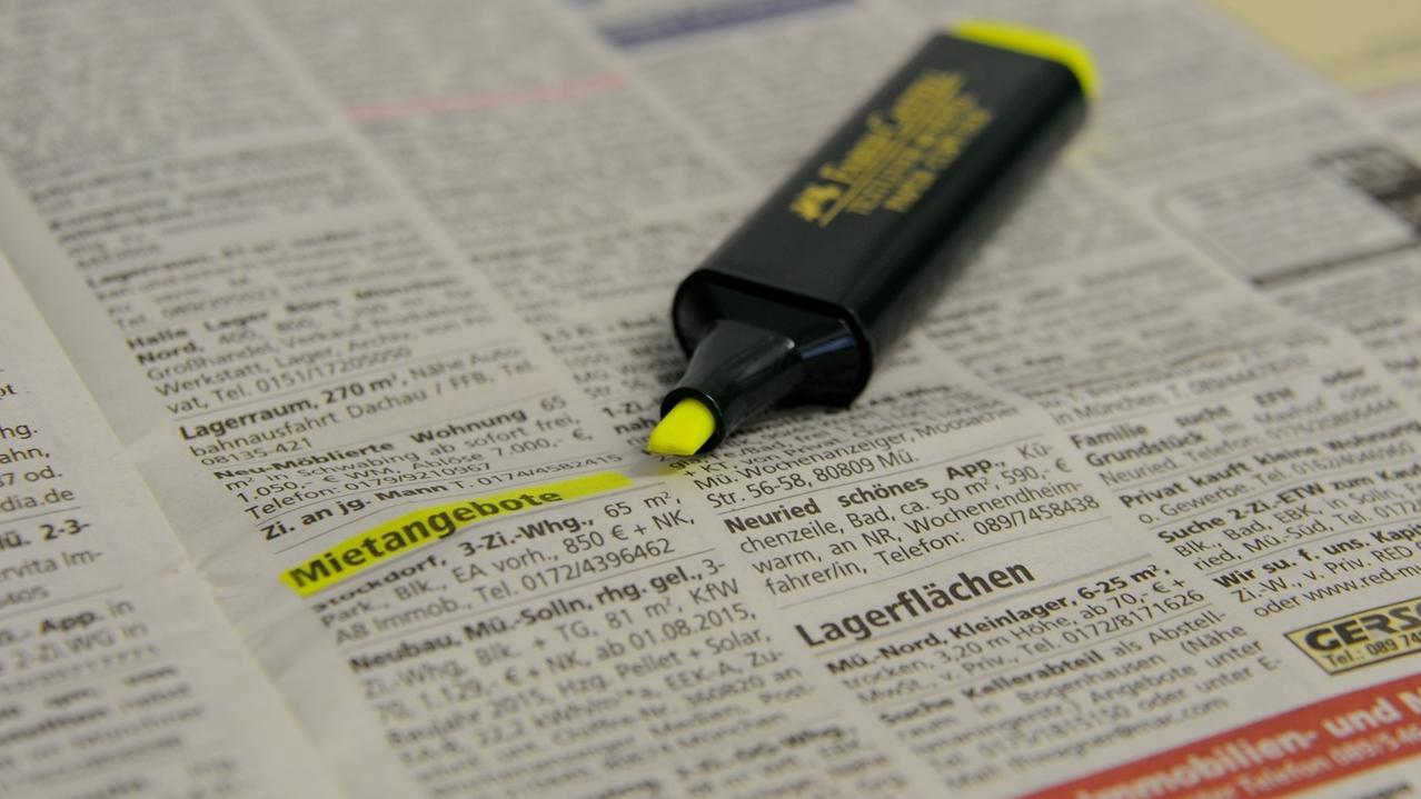 Wohnungsanzeigen in einer Zeitung, daneben liegt ein gelber Marker