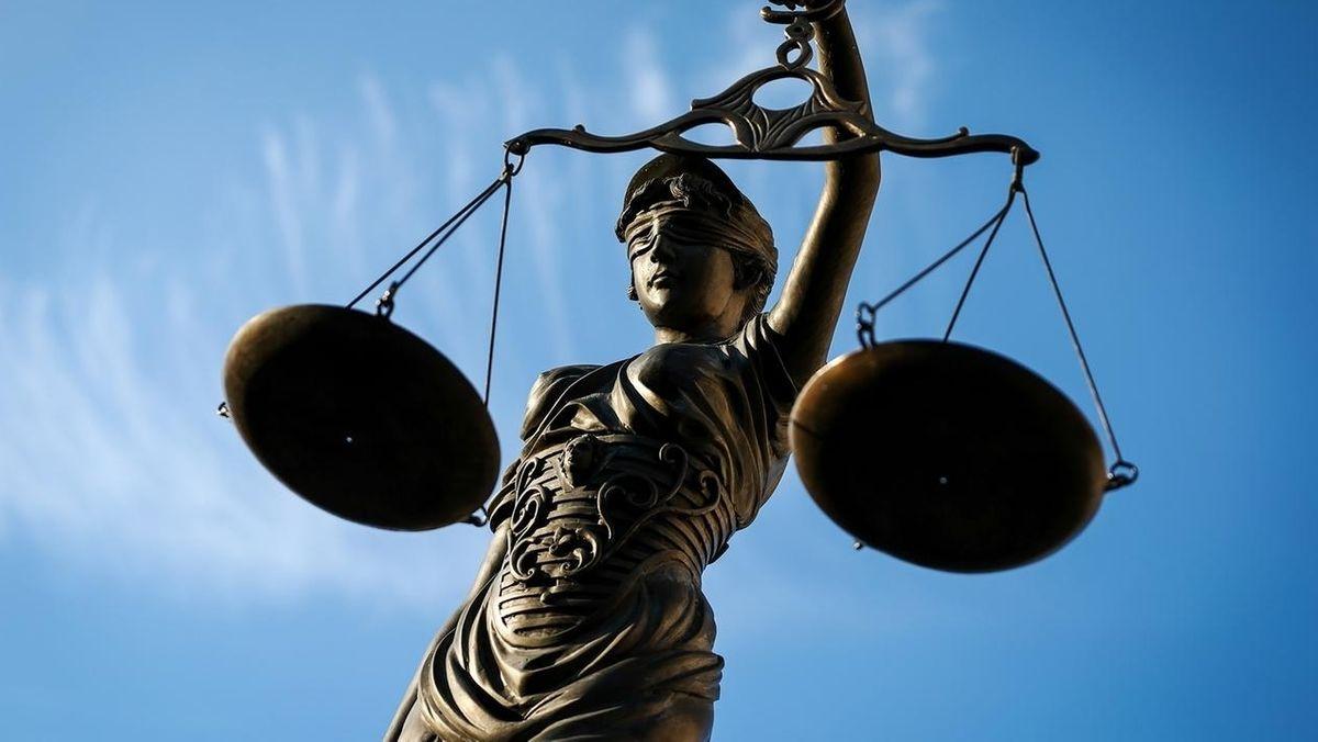 Justitia mit verbundenen Augen hält eine Waage mit zwei Waagschalen in den Händen.