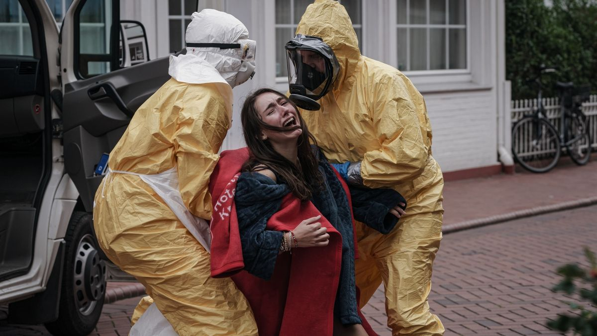 Emily Kusche wird in der Rolle als Evelin Kern von zwei Seuchenschutzmitarbeitern abgeführt.