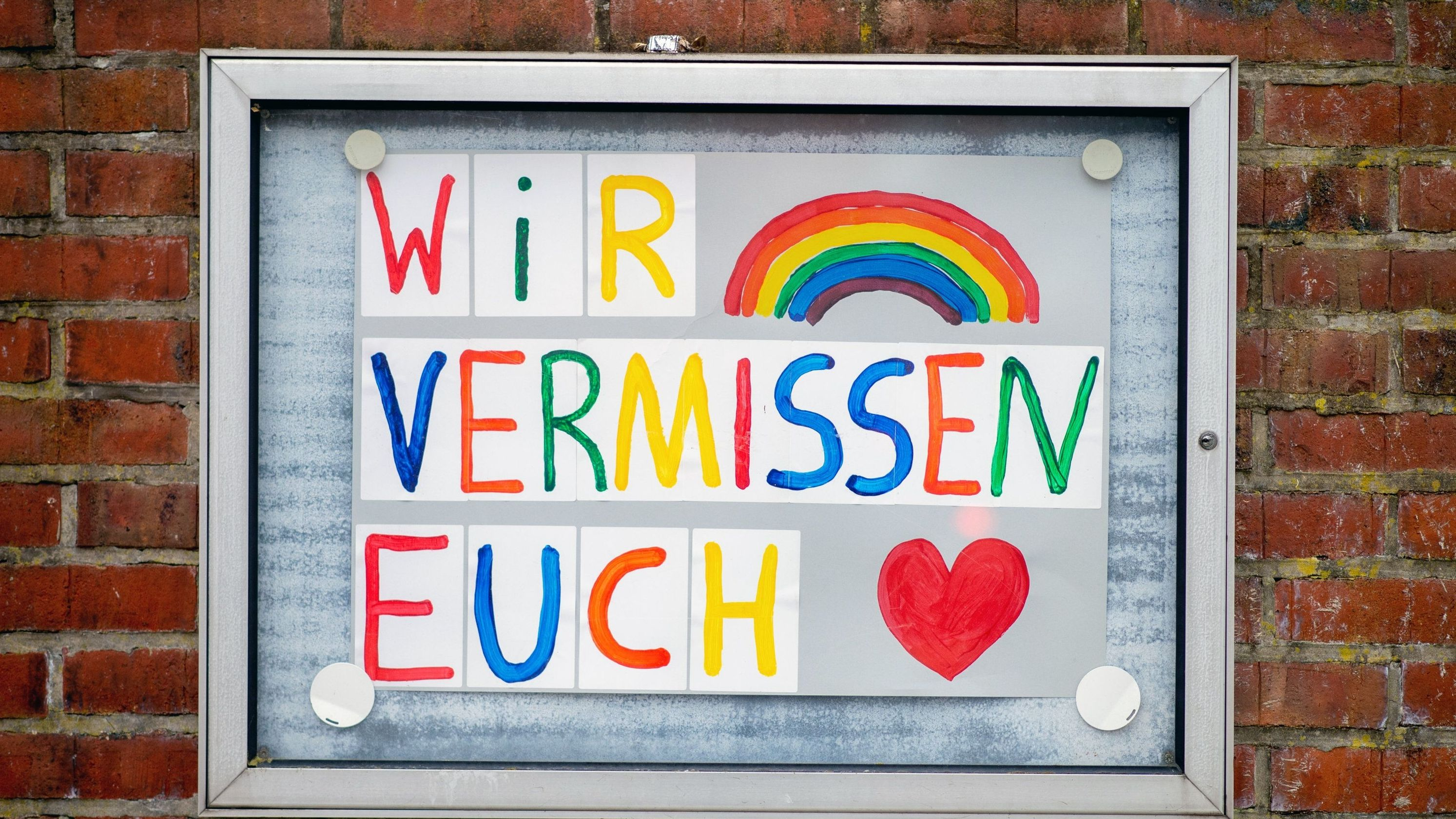 """Ein Schild mit der Aufschrift """"Wir vermissen euch"""" hängt an einem geschlossenen Kindergarten."""