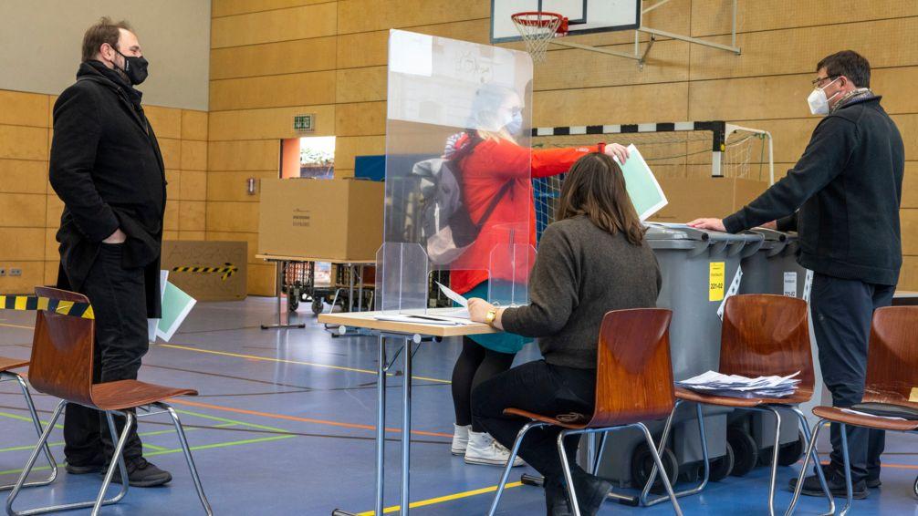 Eine Wählerin wirft im Wahllokal in einer Turnhalle ihre Stimmzettel in die Wahlurne, vor den Wahlhelfern: eine Plexiglas-Trennwand. (Symbolbild)
