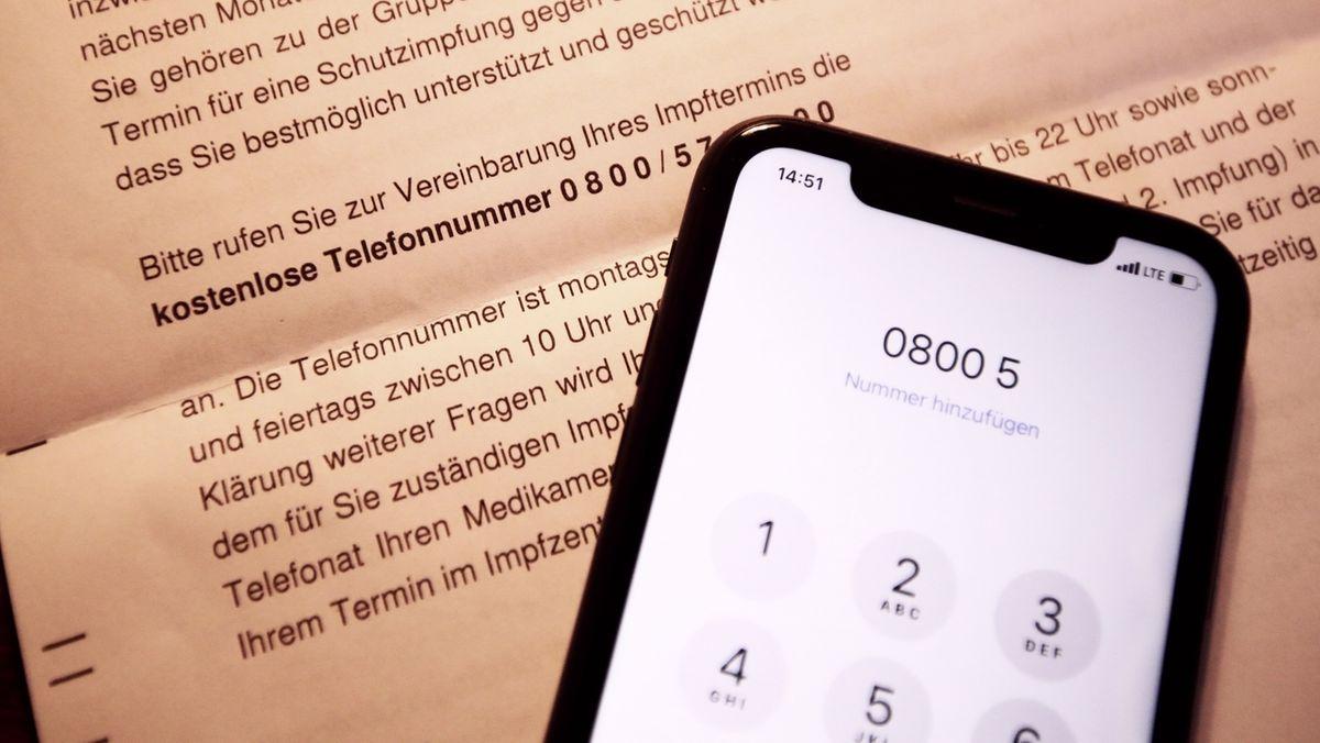 In ein Handy ist die Rufnummer der Impftermin-Vergabe eingegeben.