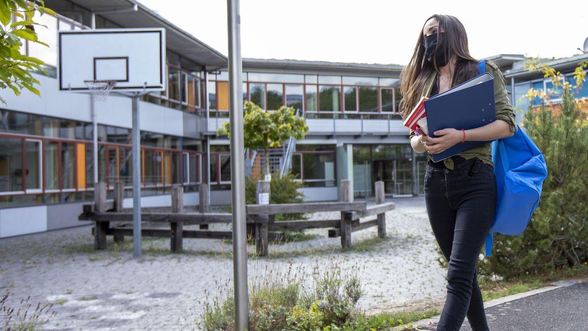 Schülerin mit Mundschutz und Schulutensilien beim Verlassen des Schulhofes