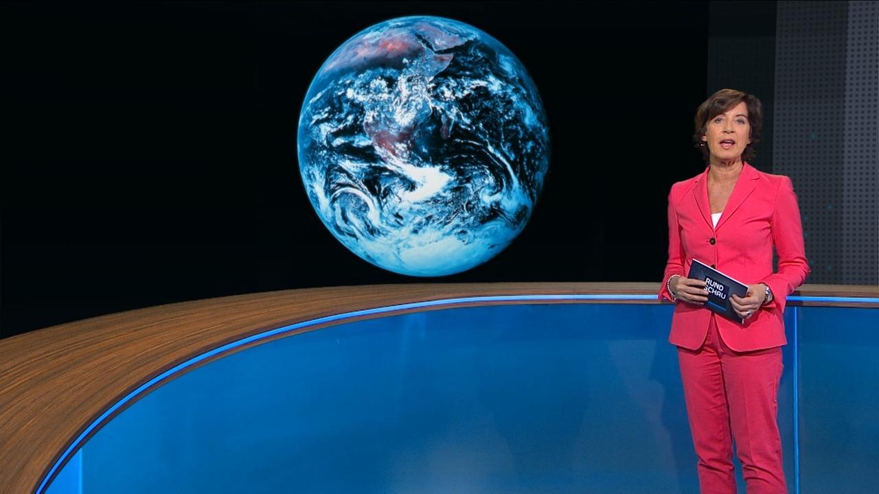 """Ursula Heller vor Bild des """"blauen Planeten"""""""