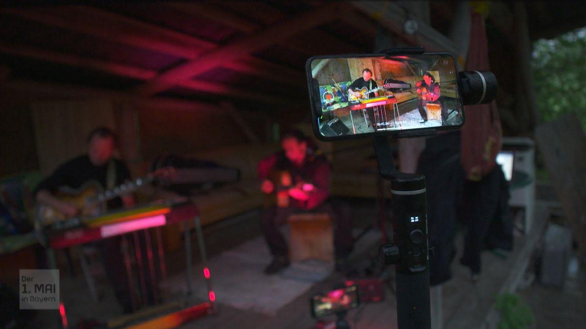 Zwei Musiker spielen unter dem Dach einen Freistandes und filmen sich mit einem Handy auf einem Stativ.