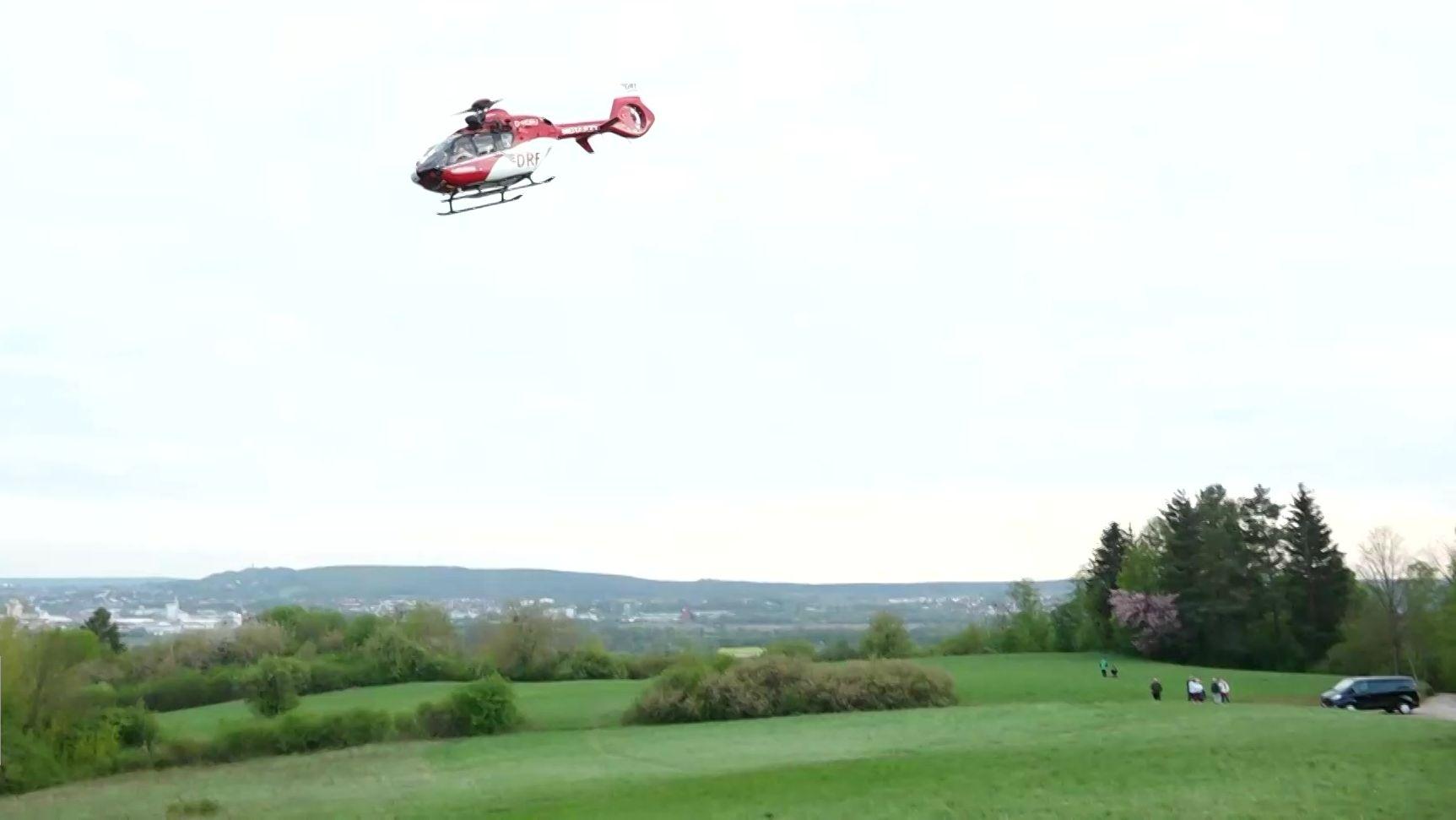 Ein rot-weißer Rettungshubschrauber fliegt über einer Wiese