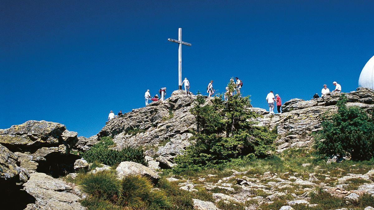 Wanderer am Gipfelkreuz des Großen Arber im Nationalpark Bayerischer Wald