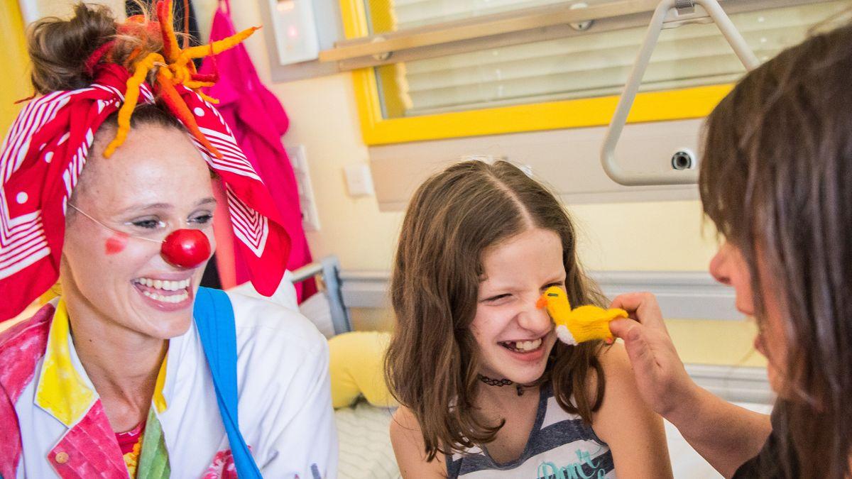 """27.06.2019, Hessen, Wiesbaden: Dr. Krümel (l-r), Clowndoktor, bringt Emma und Mutter Manuela zum Lachen. Der Verein """"Die Clown Doktoren e.V."""" ist ein Verein für den professionelle Clowns bundesweit in Krankenhäusern und Pflegeeinrichtungen tätigt sind."""