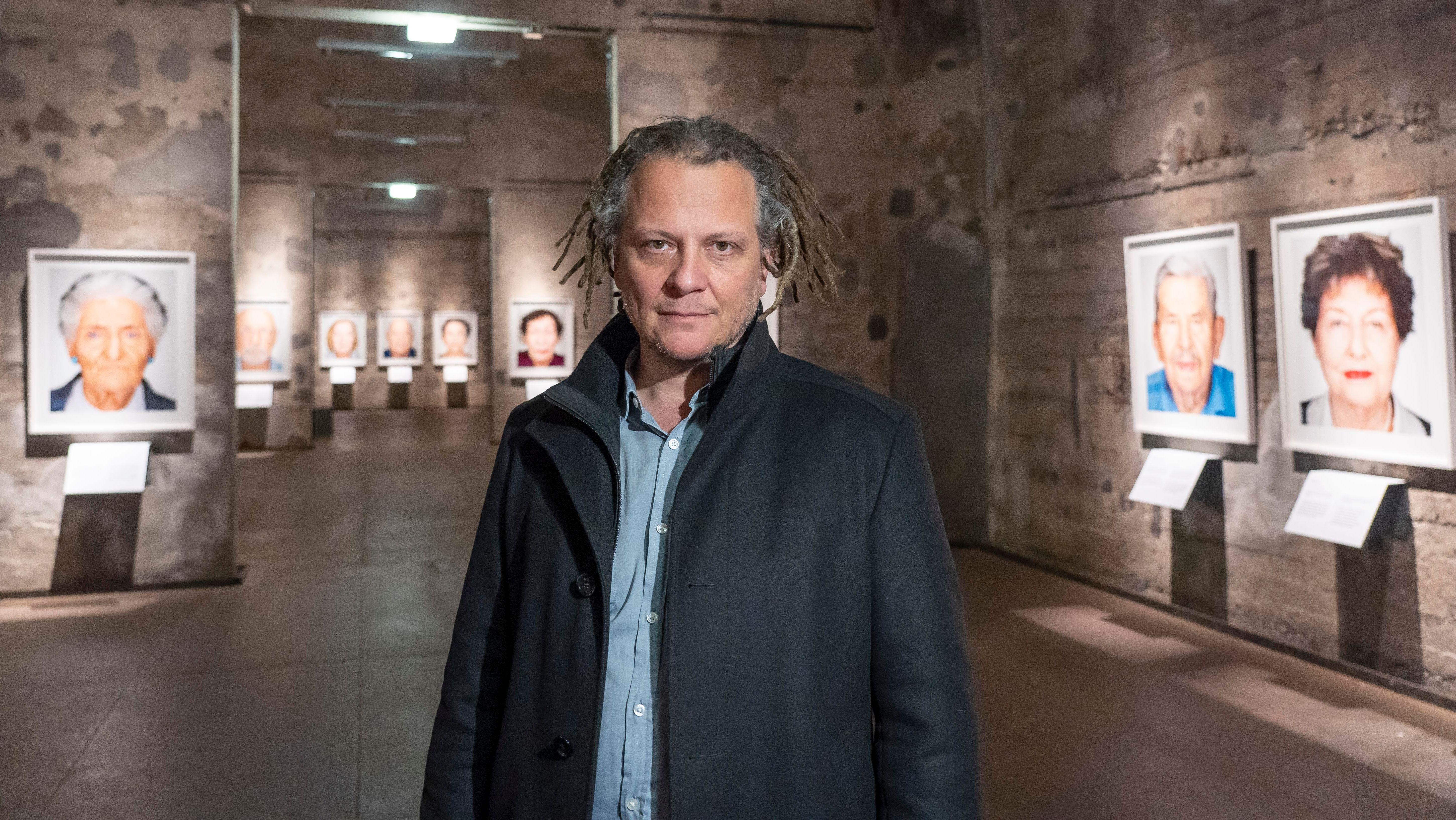 Fotograf Martin Schoeller steht vor den bewusst fleckigen Betonwänden der Essener Ausstellung, seine kinnlangen grauen Haare sind zu Dreadlocks gedreht
