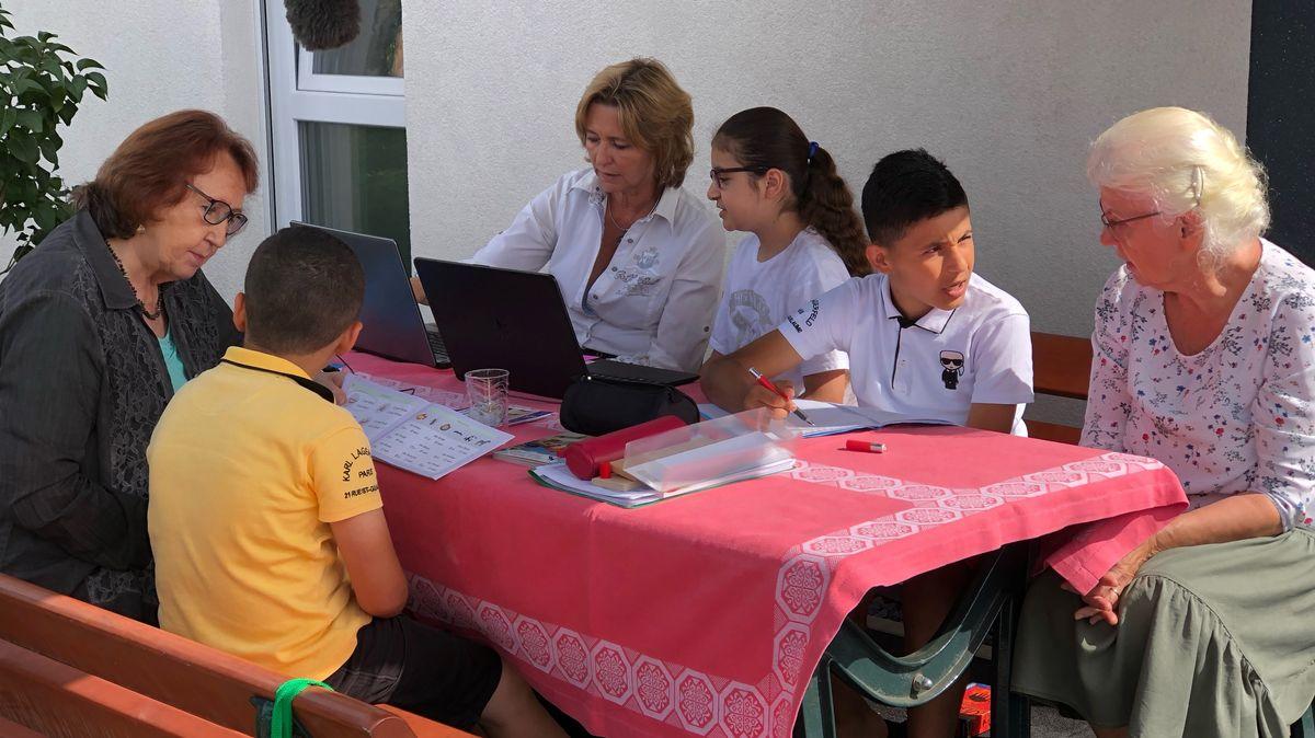 Drei Damen geben drei Kindern an einem Tisch Nachhilfe.