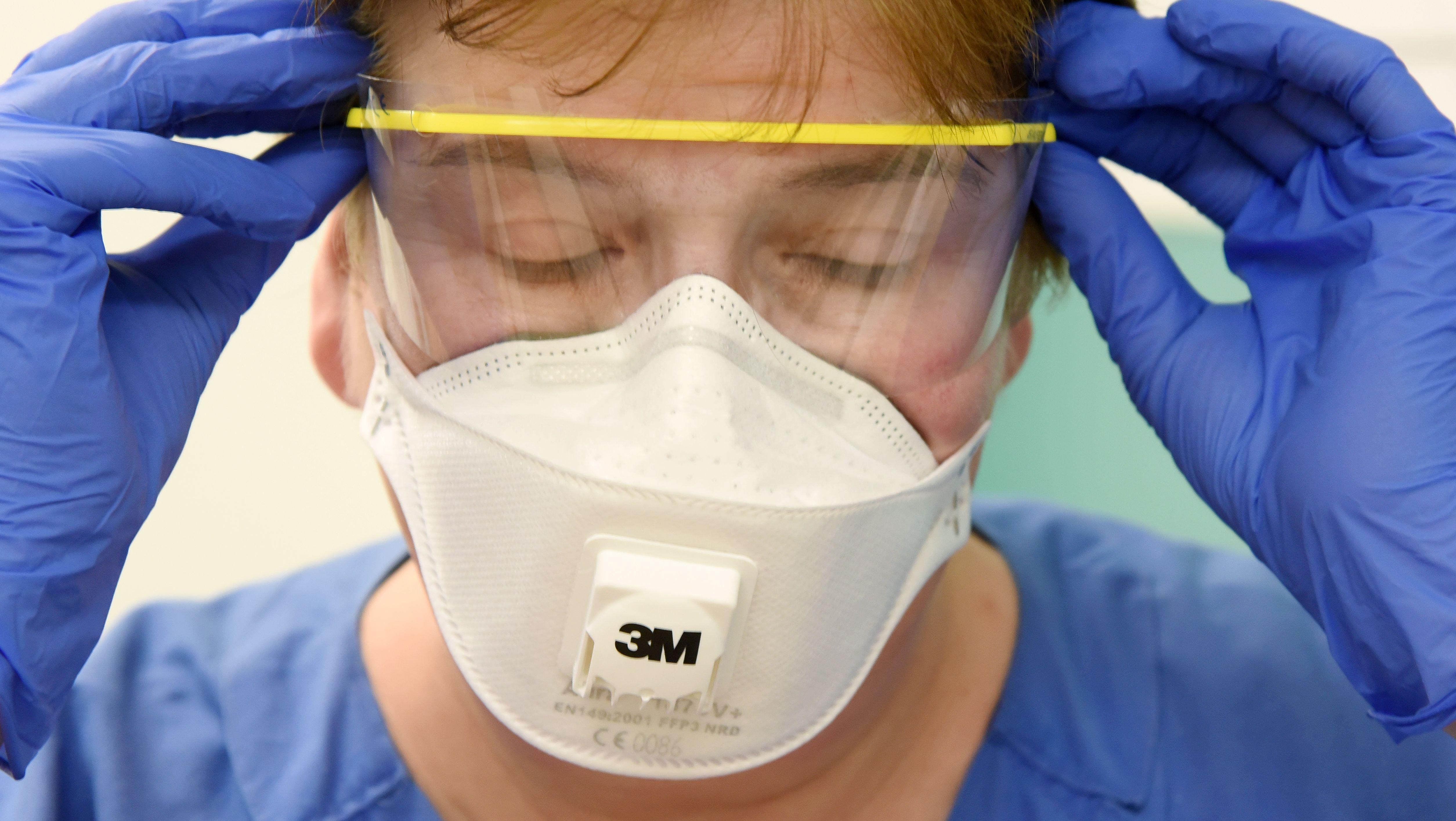 Krankenschwester trägt Mundschutz und Schutzhandschue. (Symbolbild)