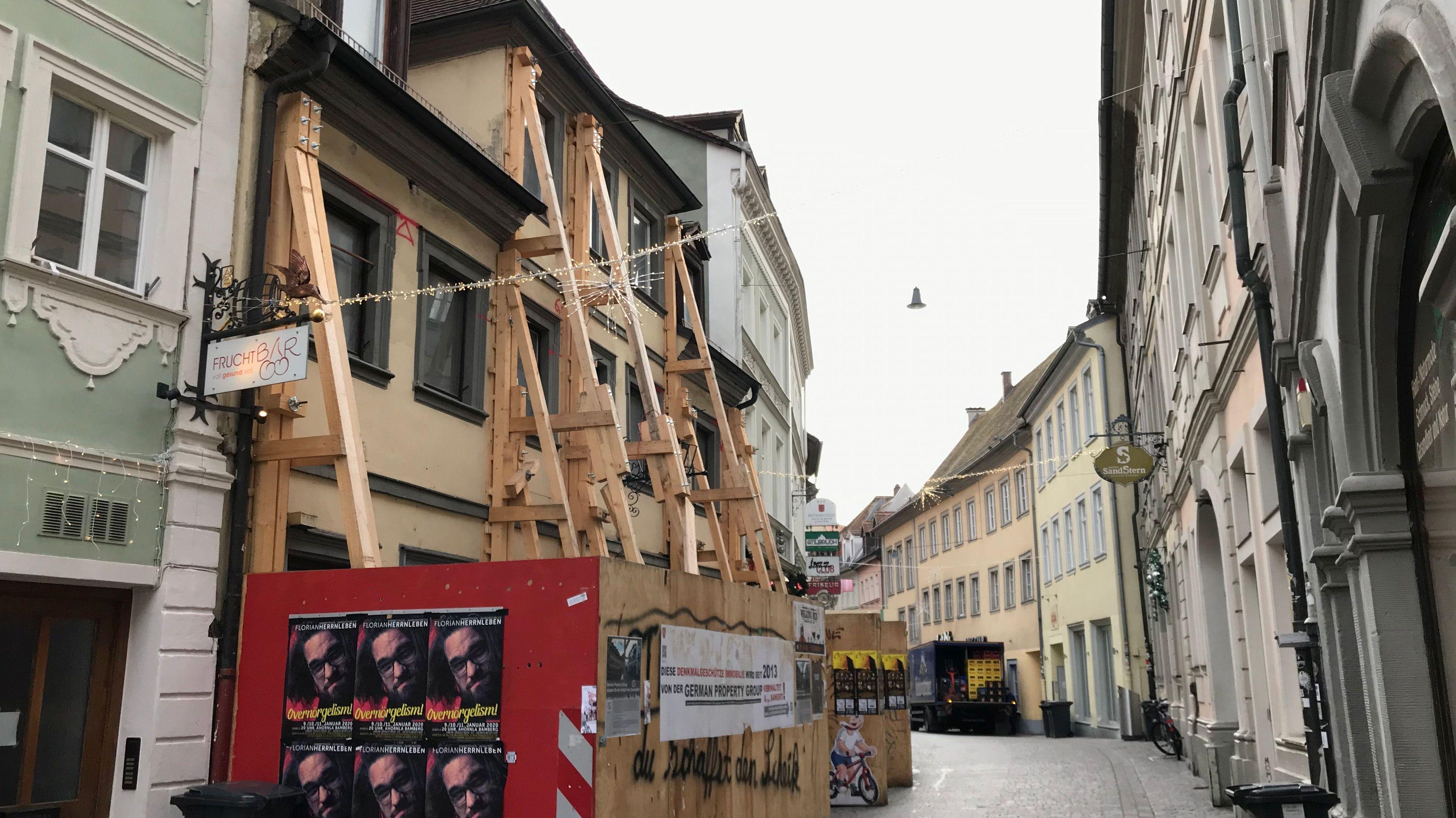 Die Fassade des einsturzgefährdeten Hauses in der Sandstraße in Bamberg ist mit Holzbalken abgestützt.