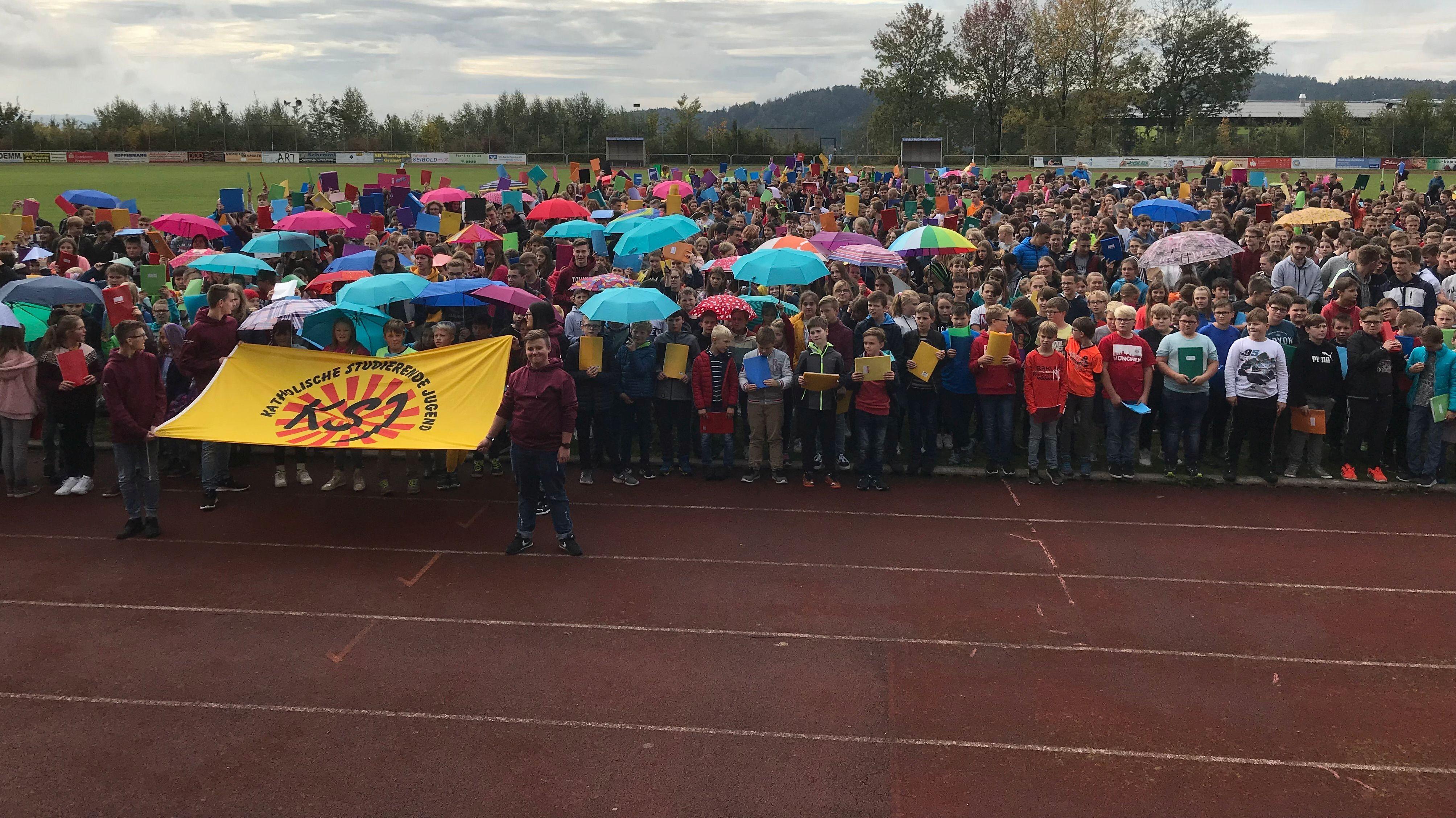 1.600 Schüler aus Freyung halten bunte Hefte und Regenschirme über ihre Köpfe, um damit ein Zeichen für Offenheit und Toleranz zu setzen