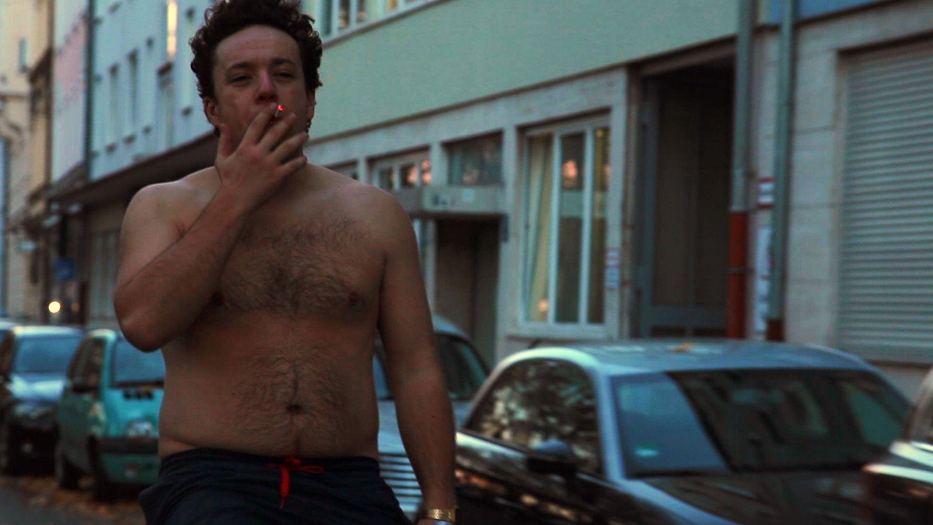 """Szene aus """"Fett und Fett, Folge 1: Alles okay"""": Jaksch (Jakob Schreier) fährt rauchend und mit nacktem Oberkörper auf einem Fahrrad eine Straße entlang."""