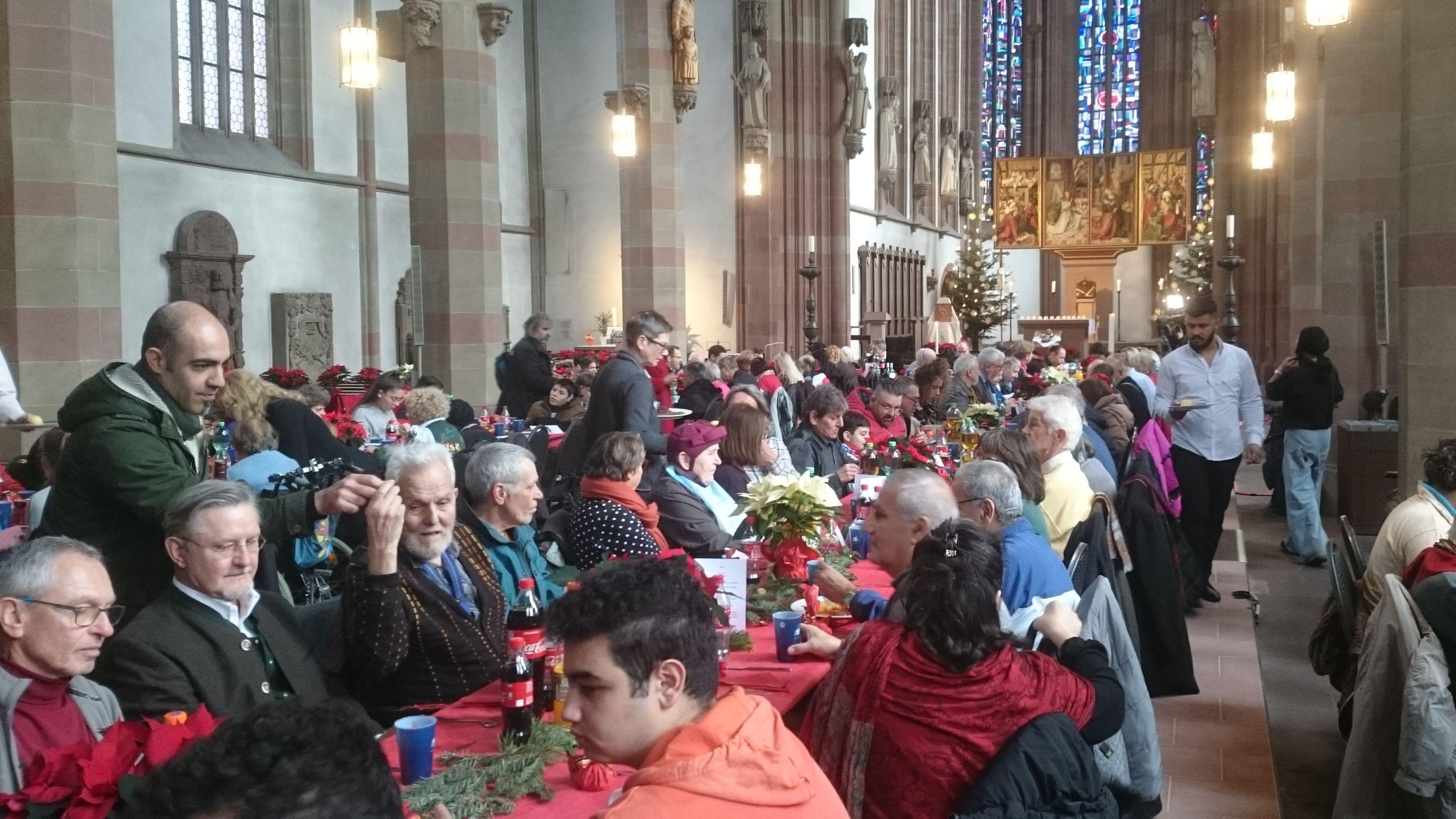 200 Menschen feierten in der Würzburger Marienkapelle an langen Tischen am 1. Weihnachtsfeiertag gemeinsam die Geburt  Jesu. Die katholische Laiengemeinschaft Sant'Egidio hatte Bedürftige, Behinderte, Flüchtlinge und Senioren eingeladen. Insgesamt bewirteten bis zu 500 ehrenamtliche Helfer über 1000 Gäste zeitgleich an fünf Orten in ganz Würzburg