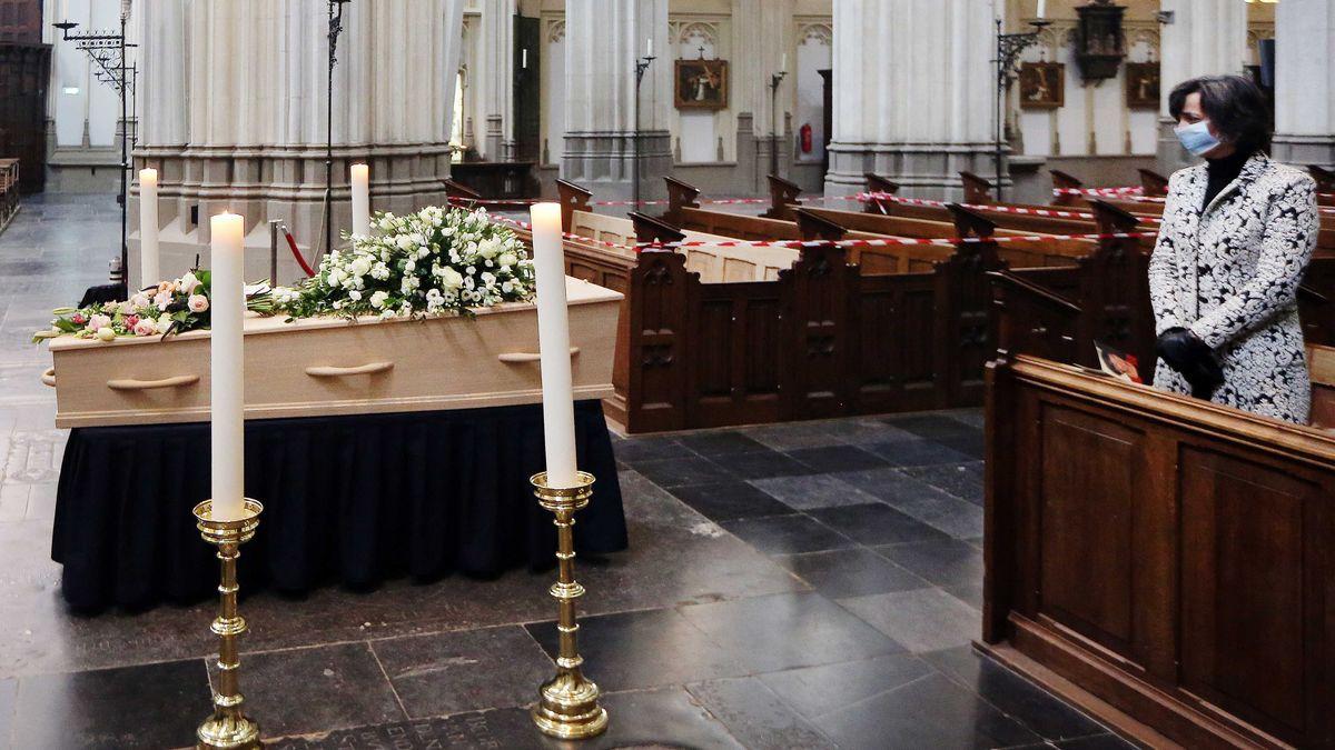 Begräbnis zur Zeit von Corona: Eine Frau steht mit Mundschutz in der ersten Reihe der Kirchenbänke und blickt auf einen mit Blumen geschmückten Sarg. Kirchenbänke im Hintergrund sind abgesperrt.