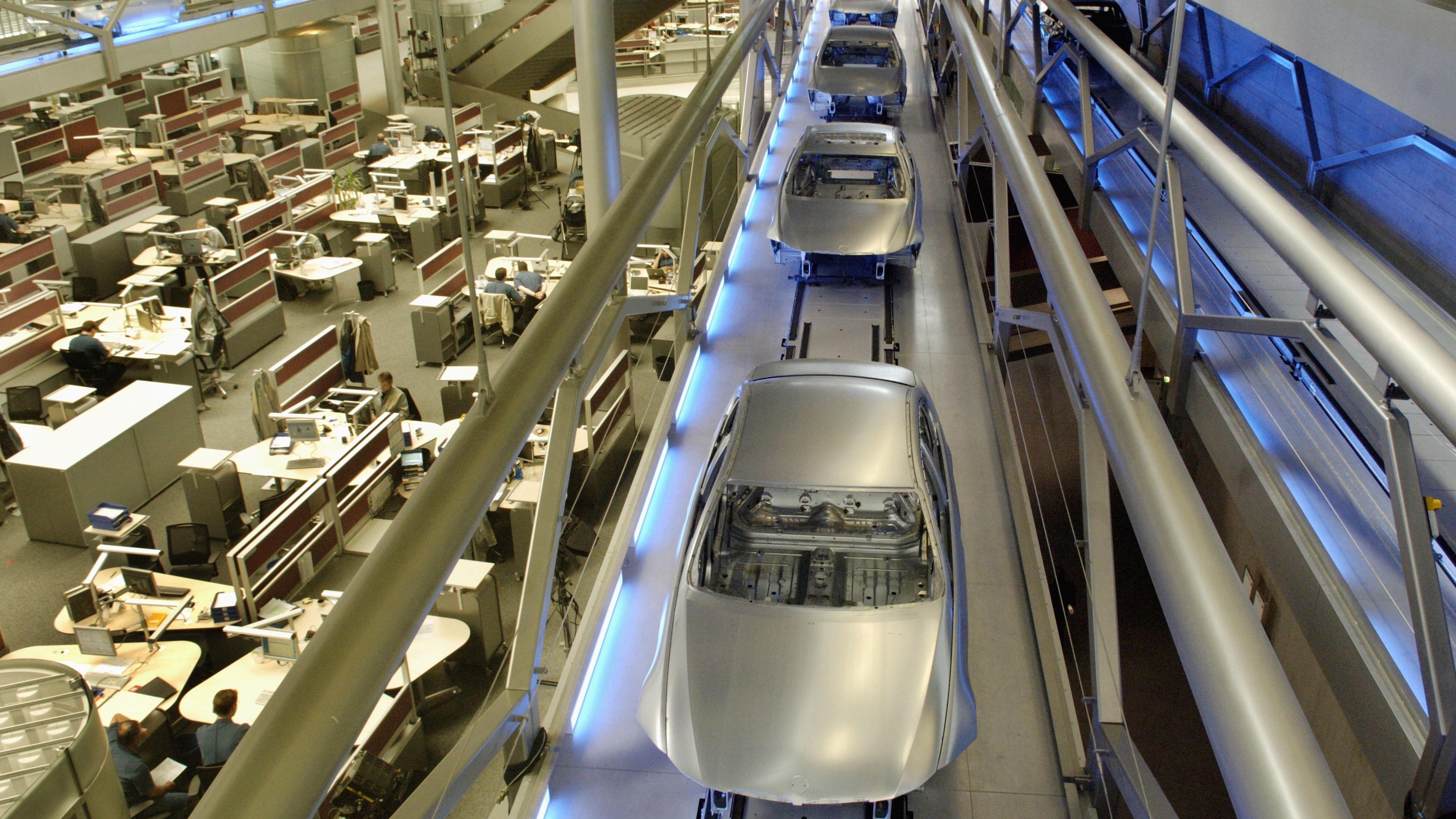 In einem BMW-Werk laufen die Karosserien der 3er-Modelle auf Bändern oberhalb der Büroetage in die Lackiererei (Symbolbild)