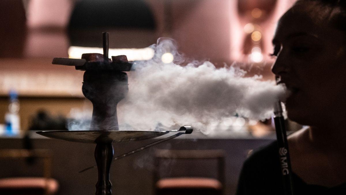Eine Frau raucht eine Shisha-Pfeife in einer Bar.