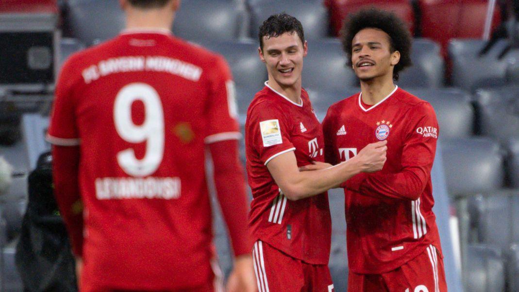 FC Bayern-Spieler Leroy Sane (r) und Benjamin Pavard (M) jubeln über ein Tor.