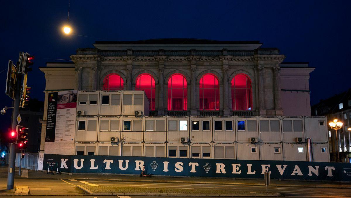 """Staatstheater Augsburg nachts mit roter Beleuchtung im Inneren. Auf einem Bannersteht: """"Kultur ist relevant""""."""